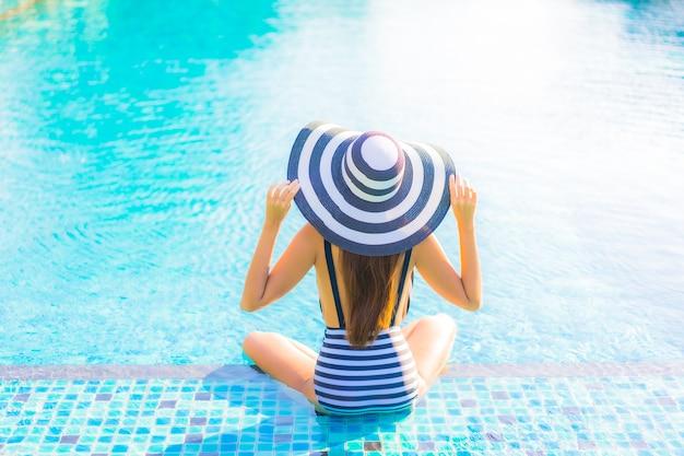 Retrato joven y bella mujer relajarse sonrisa ocio de vacaciones alrededor de la piscina en el hotel resort