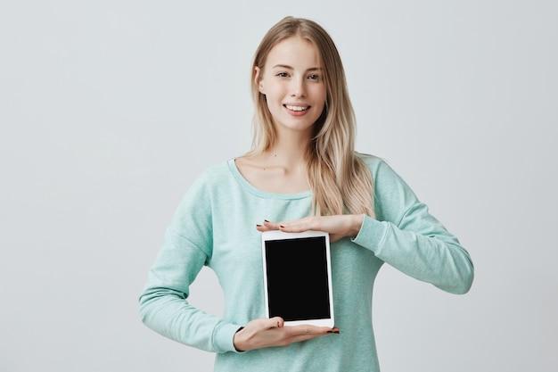 Retrato de joven bella mujer rubia sonriente sosteniendo y mostrando tableta digital en blanco