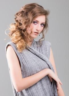 Retrato de una joven y bella mujer rubia con un vestido gris. foto de arte de moda