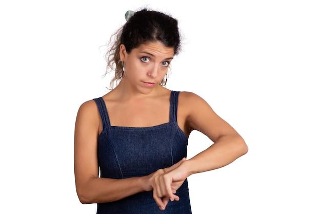 Retrato de joven bella mujer señalando con el dedo en la muñeca