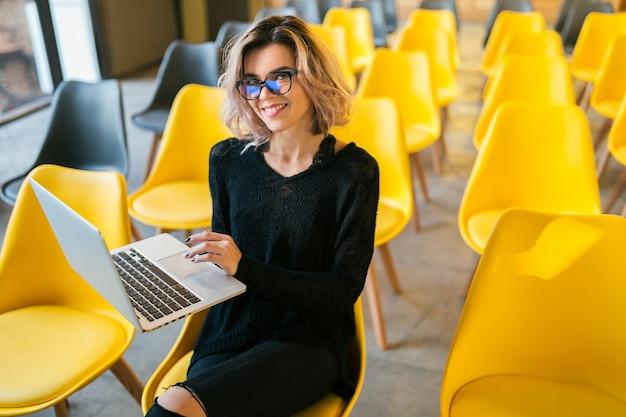 Retrato de joven bella mujer sentada en la sala de conferencias, trabajando en la computadora portátil, con gafas, aula