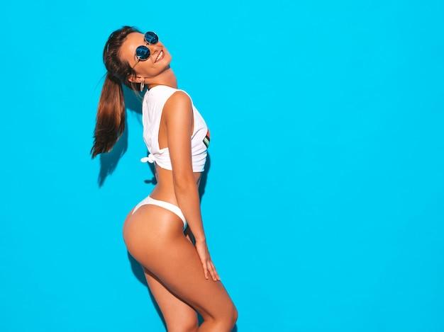Retrato de joven bella mujer sexy sonriente en calzoncillos de verano blanco y tema. chica de moda en gafas de sol. hembra positiva volviéndose loca. modelo divertido aislado