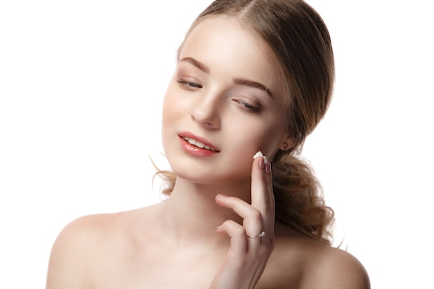 Retrato de joven bella mujer sonriendo mientras toma un poco de crema facial aislado en blanco
