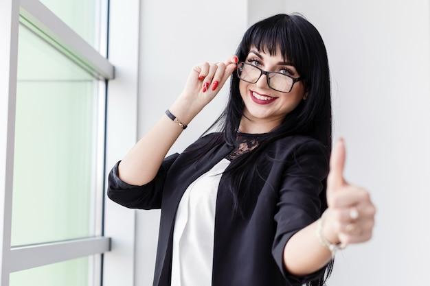 Retrato de joven bella mujer sonriente con gafas de pie cerca de la ventana