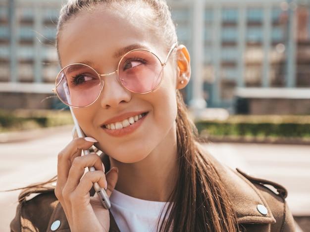 Retrato de joven bella mujer sonriente hablando por teléfono chica de moda en ropa casual de verano mujer divertida y positiva posando en la calle