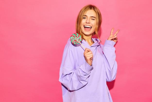 Retrato de joven bella mujer sonriente hipster en moda verano con capucha. mujer despreocupada atractiva que presenta cerca de la pared rosada. modelo positivo con piruleta que muestra el signo de la paz