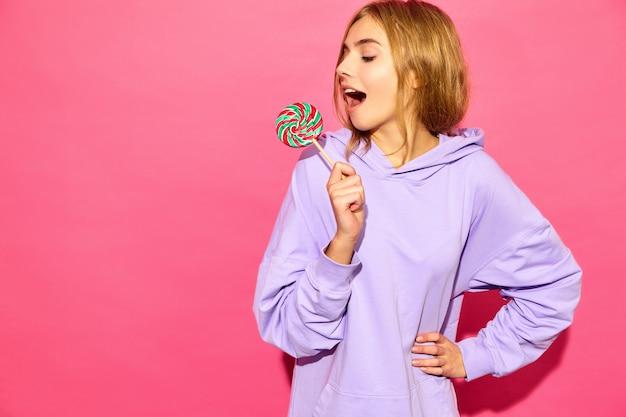 Retrato de joven bella mujer sonriente hipster en moda verano con capucha. mujer despreocupada atractiva que presenta cerca de la pared rosada. modelo positivo con piruleta