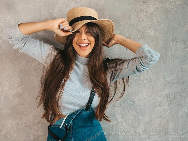 Retrato de joven bella mujer sonriente mirando. chica de moda en ropa de verano casual monos y sombrero.