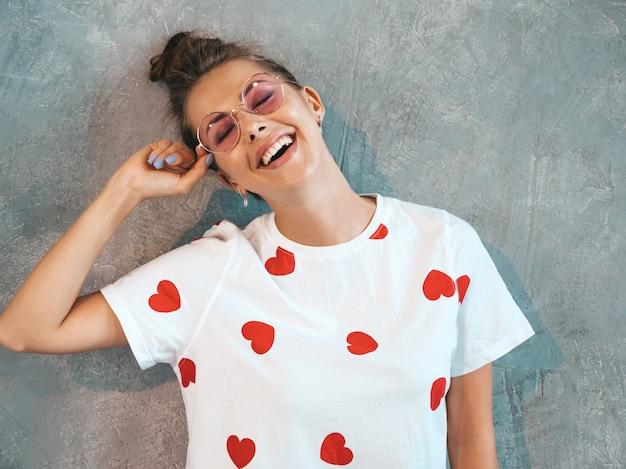 Retrato de joven bella mujer sonriente mirando. chica de moda en verano casual vestido blanco y gafas de sol.
