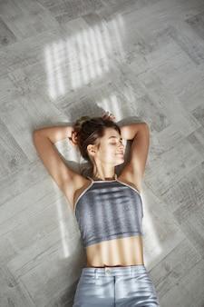 Retrato de joven bella mujer tierna con los ojos cerrados sonriendo acostado en el piso en las luces del sol de la mañana.