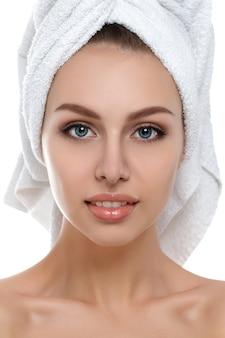 Retrato de joven bella mujer con una toalla en el pelo tocando su rostro aislado. limpieza facial, piel perfecta. terapia de spa, cuidado de la piel, cosmetología.