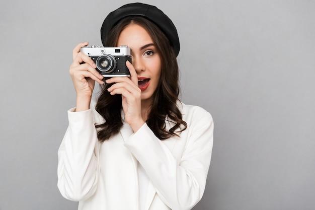 Retrato de una joven y bella mujer vestida con chaqueta sobre fondo gris, tomando fotografías con cámara de fotos