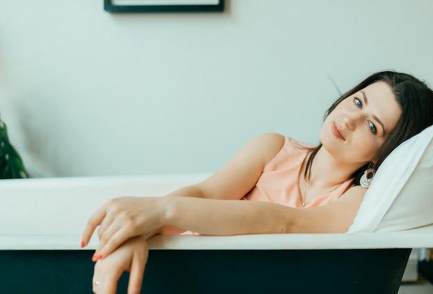 Retrato de joven bella mujer en vestido rosa tumbado en la bañera vacía de hierro fundido vintage