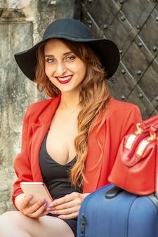 Retrato de una joven y bella mujer viajera caucásica sentada en la puerta con maleta y smartphone sonriendo y mirando a la cámara al aire libre