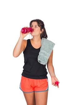 Retrato de joven bella mujer vistiendo ropa deportiva y bebiendo algo