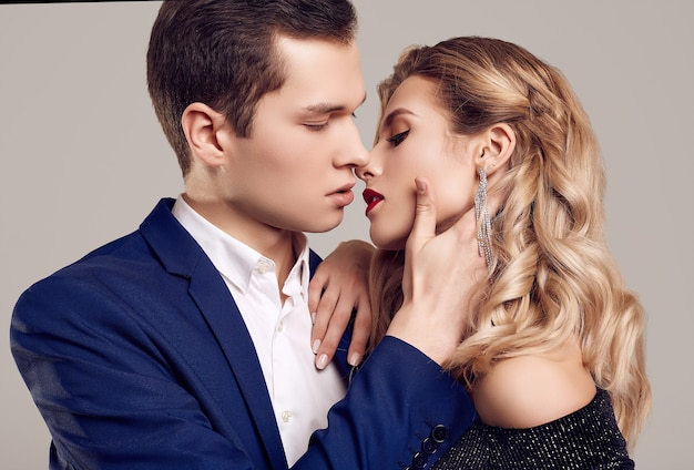 Retrato de una joven y bella pareja sensual vestida con ropa formal: mujer en vestido negro de lujo de moda y hombre vestido con traje clásico azul aislado en la pared blanca.