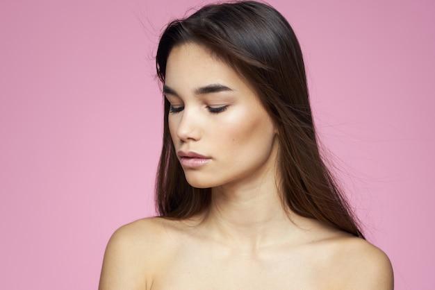 Retrato de una joven belleza sobre un fondo rosa