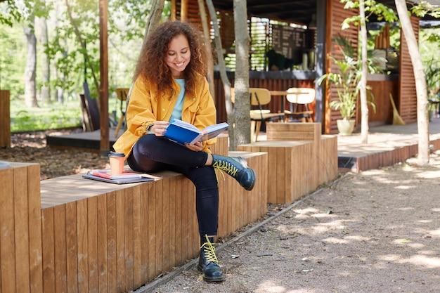 Retrato de una joven y bonita estudiante de piel oscura y rizada sentada en la terraza de un café, vestida con abrigo amarillo, tomando café y con una amplia sonrisa, disfruta estudiando, preparándose para los exámenes.
