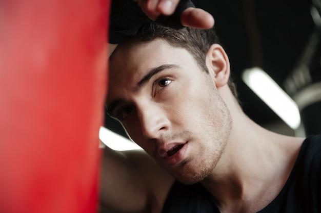 Retrato de joven boxeador centrado mirando a otro lado cerca de saco de boxeo