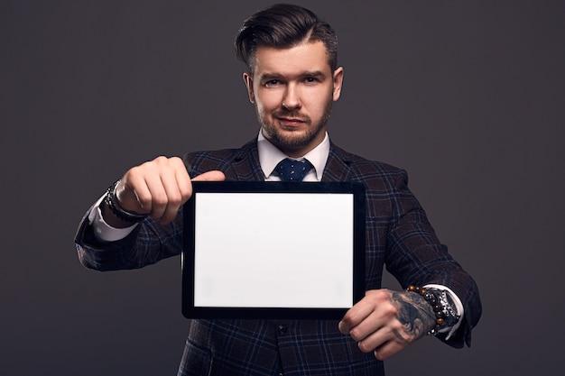 Retrato de un joven brutal elegante con tableta
