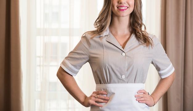 Retrato de una joven camarera con las manos en la cintura en una habitación de hotel