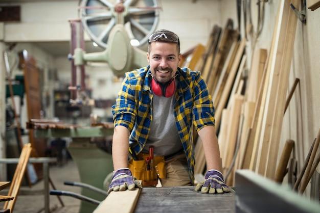 Retrato de joven carpintero motivado de pie junto a la máquina para trabajar la madera en su taller de carpintería