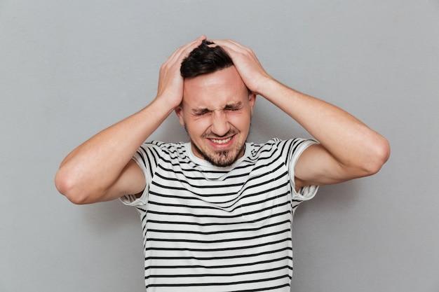 Retrato de un joven casual que sufre de un dolor de cabeza