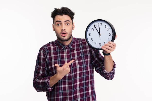 Retrato de un joven casual con reloj de pared aislado en una pared blanca