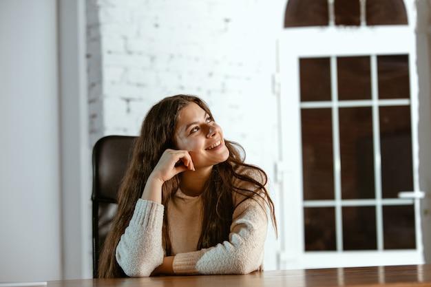 Retrato de joven caucásica en ropa casual parece soñadora, linda y feliz. mirando hacia arriba y pensando, sentado en el interior en la mesa de madera. concepto de futuro, destino, sueños, visualización.
