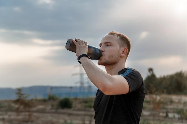 Retrato de un joven caucásico bebiendo agua de una botella después o antes del entrenamiento