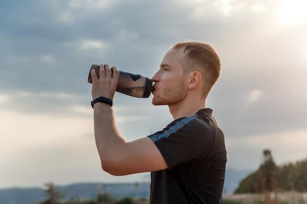 Retrato de un joven caucásico en una camiseta negra y pantalones cortos negros bebiendo agua de una botella