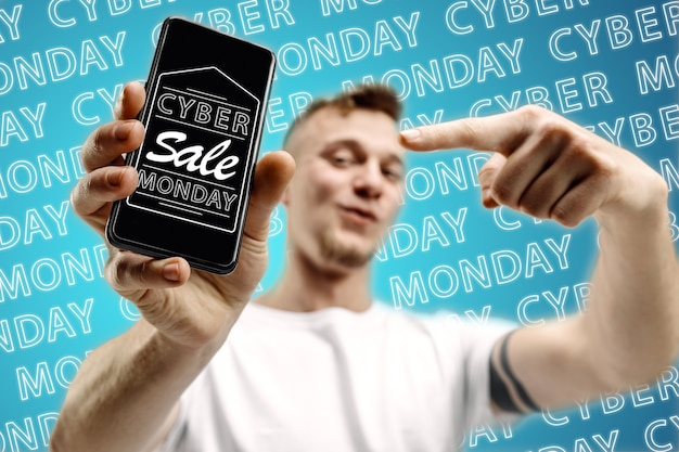 Retrato de joven caucásico mostrando la pantalla del teléfono móvil sobre fondo azul con neón