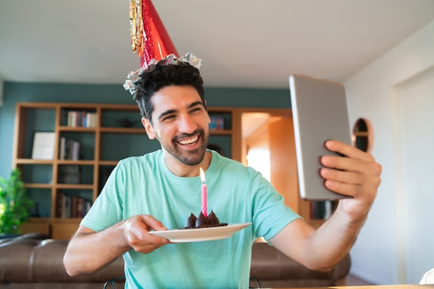 Retrato de joven celebrando un cumpleaños en una videollamada con tableta digital y un pastel con una vela en casa