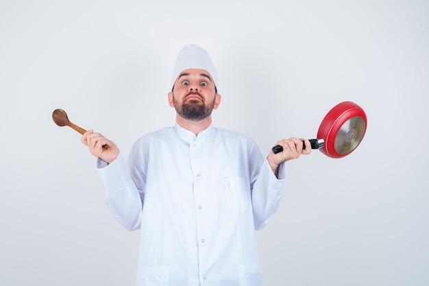 Retrato de joven chef sosteniendo una sartén y una cuchara de madera en uniforme blanco y mirando desconcertado vista frontal