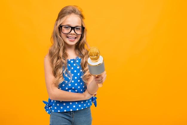 Retrato de joven chica caucásica con largo cabello rubio en gafas negras con un micrófono entrevistan y sonrisas