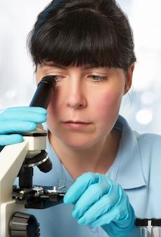 Retrato de una joven científica que trabaja con microscopio