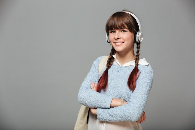 Retrato de una joven colegiala sonriente con mochila