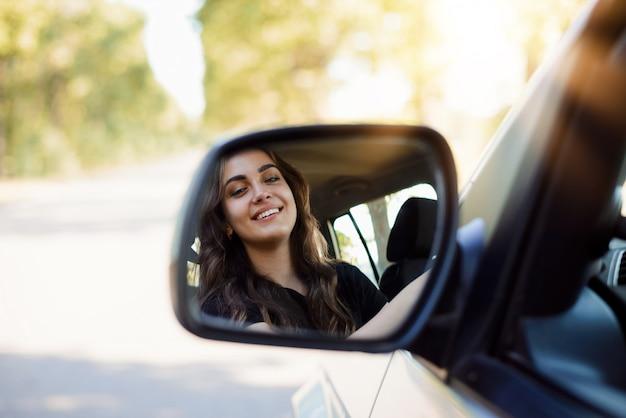 Retrato de una joven conductora a través del espejo retrovisor de un automóvil moderno