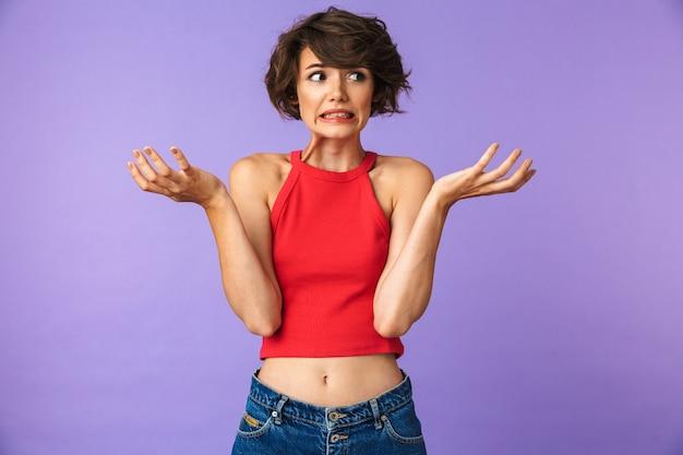 Retrato de una joven confundida encogiéndose de hombros