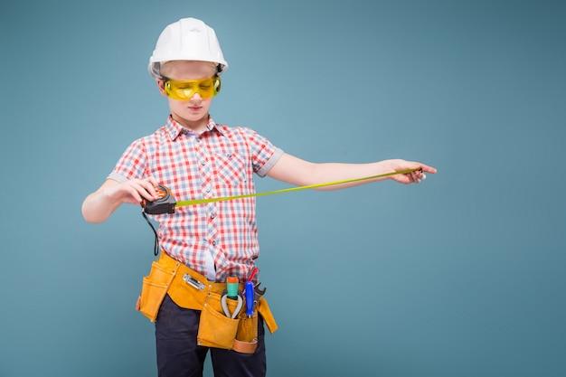 Retrato de un joven constructor en un casco y una cinta métrica en la mano