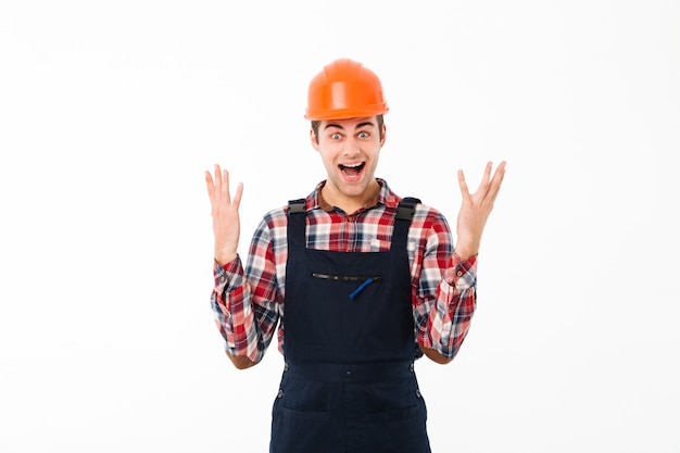 Retrato de un joven constructor masculino satisfecho celebrando