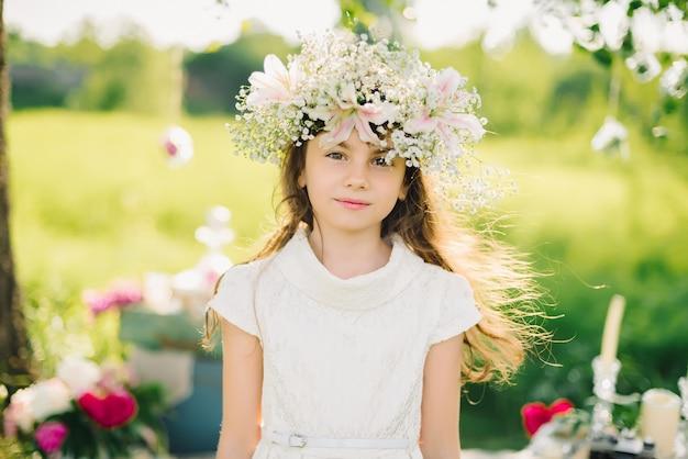 Retrato de una joven con una corona de flores en la cabeza en un prado