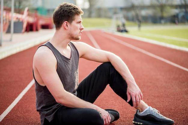 Retrato de joven corredor sentado en la pista de carreras