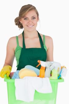 Retrato de joven criada llevando suministros de limpieza