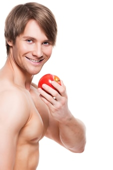 Retrato de joven culturista sonriente sosteniendo apple en su mano