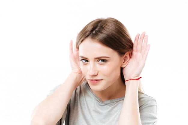 Retrato de una joven curiosa joven tratando de escuchar rumores