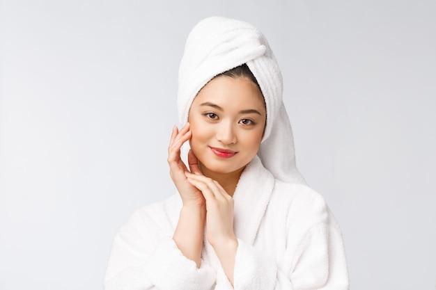 Retrato de una joven dama asiática feliz en bata de baño. aislado en el fondo blanco.