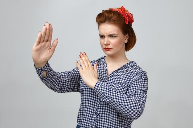 Retrato de una joven dama europea de moda seria con lápiz labial rojo, pañuelo en la cabeza y camisa a cuadros tomados de la mano frente a ella como si mostrara un movimiento de artes marciales