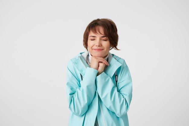 Retrato de una joven dama positiva positiva en impermeable azul, con expresiones felices, con los ojos cerrados y las manos apretadas, esperanzas de suerte y sueños sobre una buena semana, se encuentra sobre la pared blanca.