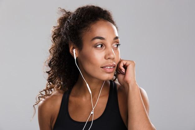 Retrato de una joven deportista afroamericana aislada sobre fondo gris, escuchando música con auriculares, mirando a otro lado